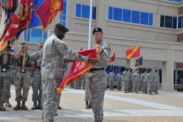 Brig. Gen. Lynn A. Collyar, U.S. Army Ordnance School commanding general and Command Sgt. Maj. Daniel A. Eubanks, Ordnance School regimental command sergeant major, unfurl the colors during the ceremony outside the Sustainment Center of Excellence Headquarters at Fort Lee, Va.