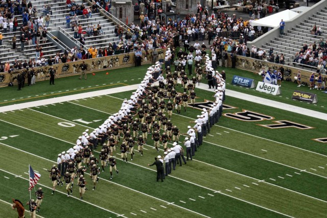 West Point cadets line the field as the football team rushes to start the game.  This is one of the many traditions practiced on Blaik Field at Michie Stadium during home football games.