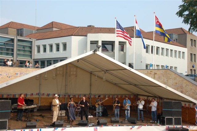 Wearing the white hat, Wilfried Dabekaussen, the Public Affairs Director for the Municipality of Schinnen, shares the stage outside the Schinnen Town Hall with USAG Schinnen Commander Lt. Col. Fern O. Sumpter (to his left) and the Supreme Headquarters Allied Powers Europe Task Force X band during the Town of Schinnen's Celebration Sept. 20 to mark 65 years of their liberation by U.S. forces in Sept. 1944.