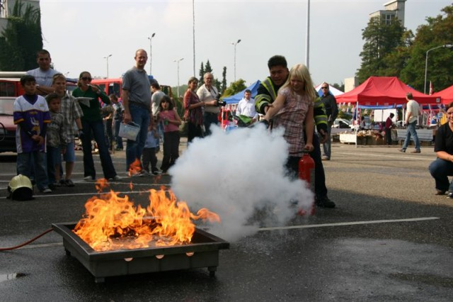 The Town of Schinnen Fire Department joined USAG Schinnen's celebration with a display Sept. 19. Here, children and spectators learn how to extinguish a grease fire. The fest on Sept. 19 included over 35 rides, bands, vendors, re-enactors, booths and other demonstrations.