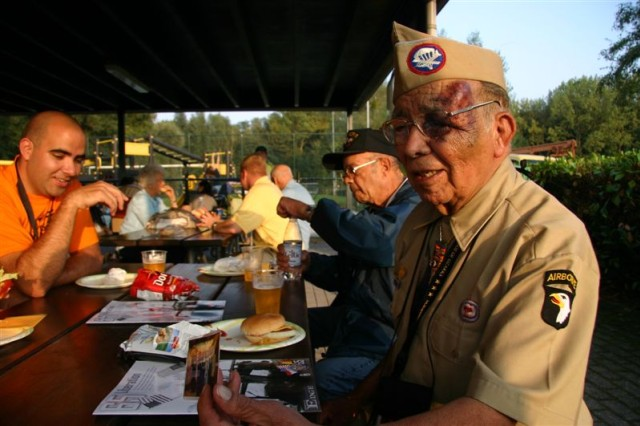 Guadelupe Flores, a World War II Veteran from Toledo, Ohio, was assigned to Headquarters and Headquarters Company. 1st Battalion, 501 Parachute Infantry Regiment, 101st Airborne Division. He is seen here tucking in some chow with the Headquarters and Headquarters Detachment, USAG Schinnen Family Readiness Group at their barbecue stall during a day of celebration on the on the only U.S. Army garrison in the Netherlands Sept. 19, 2009.  Flores jumped in during the Normandy invasion and participated in Operation Market Garden in 1944. He also was in Bastogne Dec. 16, 1944 to Jan. 30, 1945. He was part of a group of other World War II Veterans touring the Benelux area to attend Operation Market Garden Commemorations. Their group is supported by the Operation Market Garden Committee, the Greatest Generation Foundation, and were escorted by students from the College of the Ozarks, from Point Lookout, Missouri.