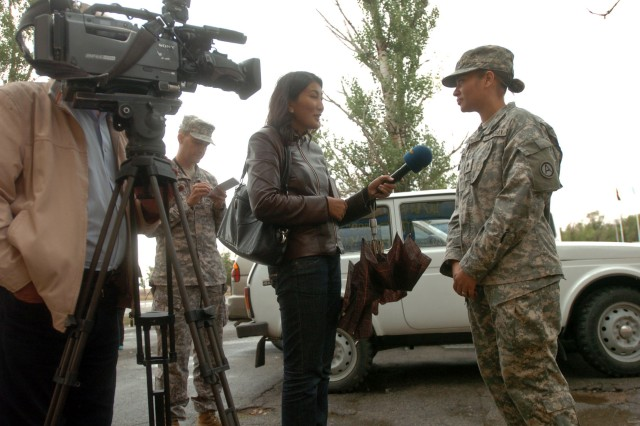 CAMP ILLISKY, Kazakhstan (Sept. 22, 2009) -On a rainy day, a reporter from the TV station Habar asks Staff Sgt. Jessica Poirrier, Third Army/U.S. Army Central Paralegal non-commissioned officer, a question about army life during a visit to the Steppe Eagle exercise at Camp Illisky, Kazakhstan, Sept. 22. Steppe Eagle is an information exchange between the U.S., British, and Kazakhstan Army that is maintaining forces' abilities to talk with one another while working in a coalition environment. (Photo by Sgt. Beth Lake, Third Army/USARCENT Public Affairs)