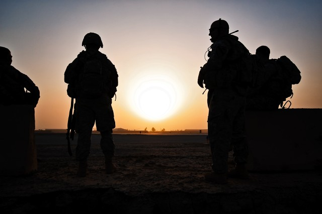 TAJI, Iraq-The sun rises as Soldiers of Company F, 3rd Battalion, 227th Aviation Regiment, 1st Air Cavalry Brigade, 1st Cavalry Division, Multi-National Division - Baghdad, wait in the early morning for two UH-60 Black Hawk helicopters to pick them and bring them to a nearby town to conduct a patrol, Sept. 18