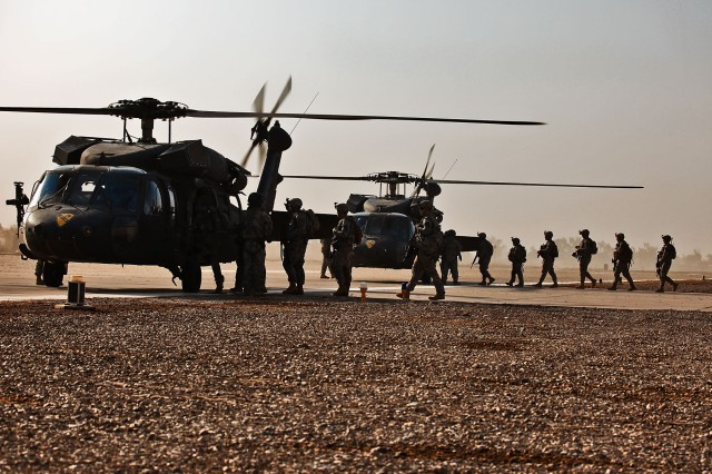 TAJI, Iraq-Loading on Black Hawk helicopters, Soldiers of Company F, 3rd Battalion, 227th Aviation Regiment, 1st Cavalry Brigade, 1st Cavalry Division, Multi-National Division - Baghdad, prepare to fly to a nearby town and conduct a presence patrol, Sept. 18.