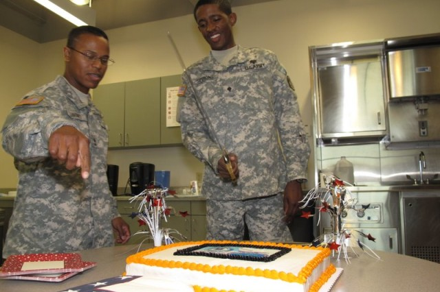 Sgt. First Class Ramon Quinones instructs Spec. Kenneth Simmons on the finer points of cake cutting.  Monday, June 15, 2009 at the Robertson Blood Center on Fort Hood.