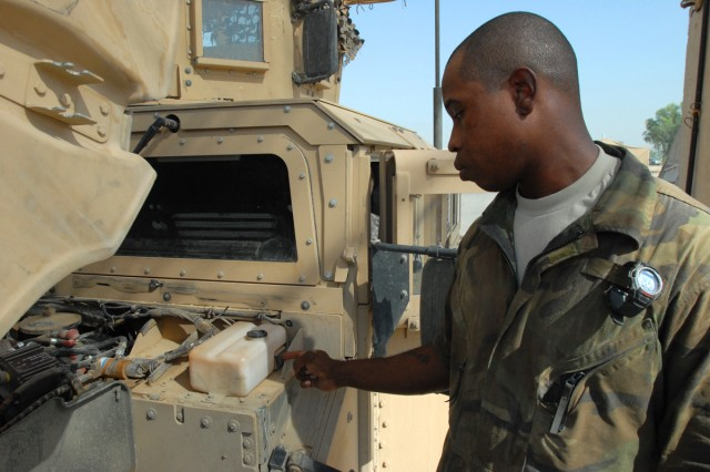CAMP LIBERTY, Iraq - Spc. Edric Ashley, a light-wheel vehicle mechanic, from Houston, indicates where the motor to the windshield washer fluid is found under the hood of a humvee, here, Sept. 22.  It is below the reservoir for windshield wiper fluid.
