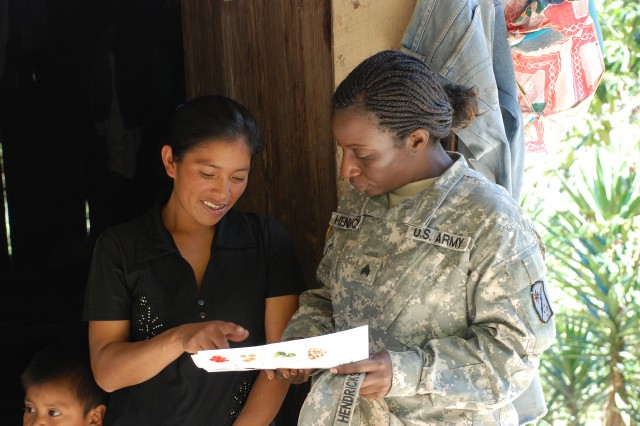 Sgt. Onika Hendricks discusses local foods high in iron and other nutrients with a mother living in the mountains near Soto Cano Air Base, Honduras.