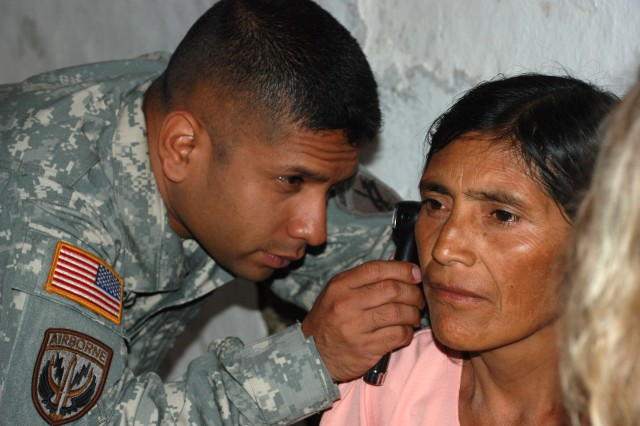 Sgt. Richard Cochea, a medical technician with Joint Task Force-Bravo's medical element, examines a Honduran woman with an ear infection at a health fair in Santa Ana, Honduras, March 24.