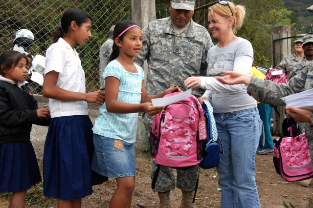 Give a Kid a Backpack Foundation volunteer Amy Vazquez and Staff Sgt. Wirient Cuevas-Salas, Joint Task Force-Bravo Civil Affairs, pass out backpacks Feb. 24 at Eseuela Nuevo Mundo in El Encinal, Honduras.