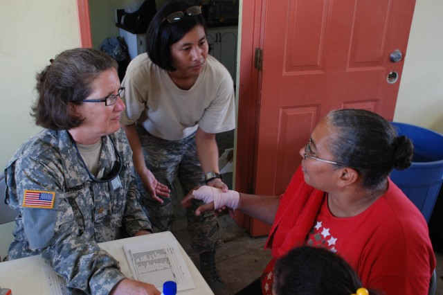Maj. Nancy Gormley, a nurse from the JTF-Bravo Medical Element, and Air Force Staff Sgt. Kat Mansfield, an emergency medical technician, help a patient during a disaster relief medical mission Nov. 13 in Burrell Boom, Belize. More than 600 people were seen by U.S. and Belize military medical personnel in two villages.