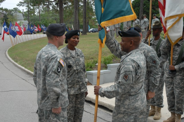 Command Sgt. Maj. Gary Newsome, who made history of his own as the first commandant of the consolidated Drill Sergeant School, passes the guidon during a change of responsibility ceremony Tuesday.