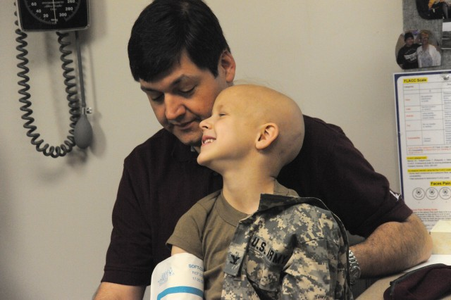 Evan sits on his dad's lap to get his blood pressure checked during a routine checkup.