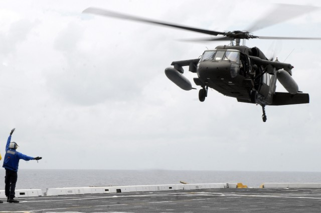 9/21/2009 - USS MESA VERDE, Panama - An Air department Sailor guides in an Army UH-60 Blackhawk, assigned to Joint Task Force-Bravo, onto the flight deck of the amphibious dock landing ship USS Mesa Verde (LPD 19) during deck landing qualifications Sept. 14. Mesa Verde is underway for Fuerzas Alidas (FA) PANAMAX 2009. FA PANAMAX is an annual U.S. Southern Command joint and multi-national training exercise tailored to the defense of the Panama Canal, involving civil and military forces from around the world. (U.S. Navy photo/Mass Communication Specialist 3rd Class Patrick Grieco).