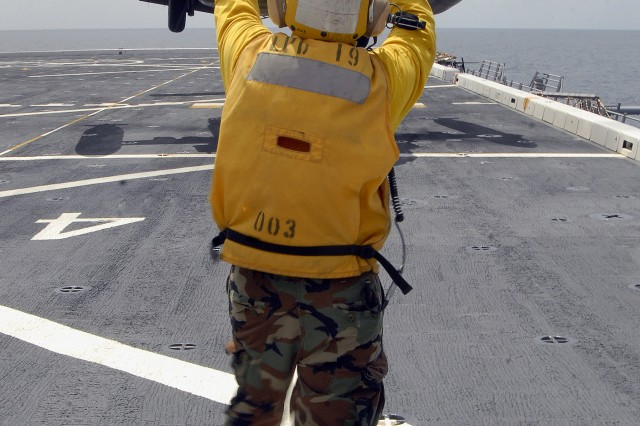 9/21/2009 - USS MESA VERDE, Panama - An Air department landing signal enlisted Sailor guides an Army UH-60 Blackhawk, assigned to Joint Task Force-Bravo, as it lifts off the flight deck of the amphibious dock landing ship USS Mesa Verde (LPD 19) during deck landing qualifications Sept. 14. Mesa Verde is underway for Fuerzas Alidas (FA) PANAMAX 2009. FA PANAMAX is an annual U.S. Southern Command joint and multi-national training exercise tailored to the defense of the Panama Canal, involving civil and military forces from around the world. (U.S. Navy photo/Mass Communication Specialist 3rd Class Patrick Grieco).