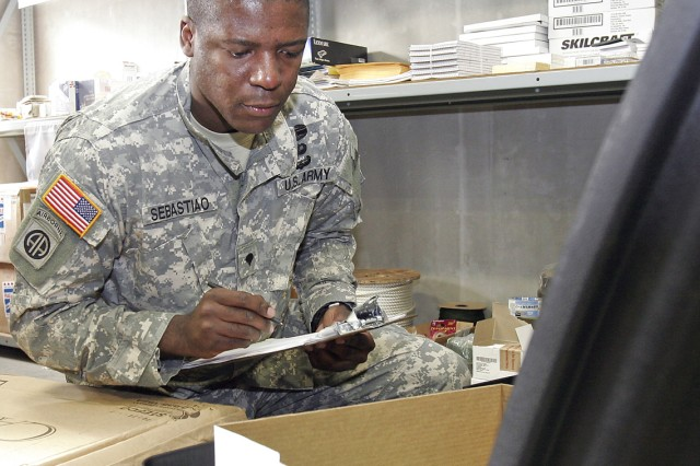 Specialist Claudio Sebastio, a supply specialist for Task Force 35, inventories the content of a recently received supply container.