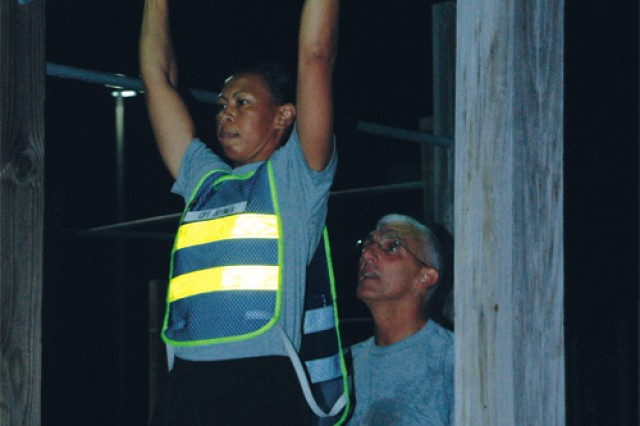 """Hertling spots Capt. Felicia Joyner, commander of E Company, 1/222nd Aviation Regiment, at the pull-up bar. Hertling started his visit to Fort Eustis with an early-morning physical training session with the E Co. """"Eagles."""""""