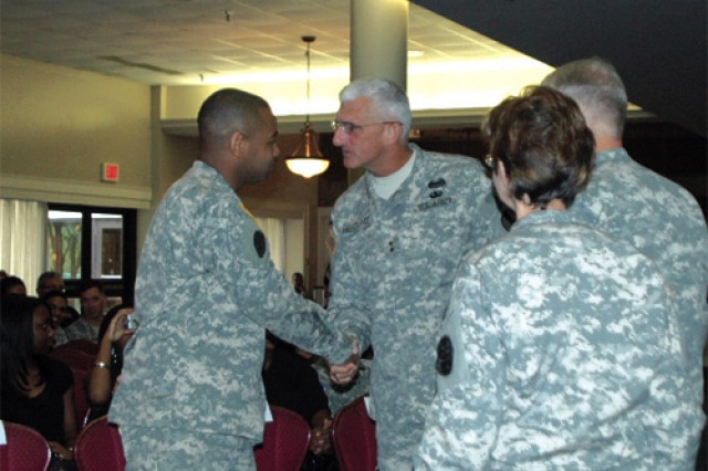 Hertling congratulates Purple Heart Medal recipient Spc. Lapatrick Black as Fort Eustis Commander Brig. Gen. Brian R. Layer and McDonald Army Health Center Commander Col. Karen Gausman look on following the award ceremony at the Fort Eustis Club Sept. 17.