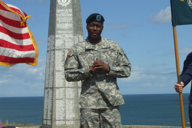 Sgt. 1st Class Charles L. Robinson III gives his promotion speech on Normandy Beach in front of the 1st Infantry Division memorial. Robinson deployed to Iraq with the 1st Infantry Division before being assigned to Alpha Detachment, 1st Space Company (JTAGS-Europe).