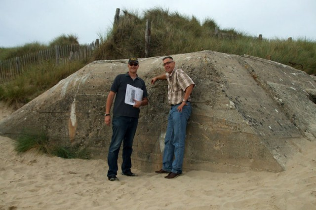 U.S. Army Space and Missile Defense Command/Army Forces Strategic Command Chaplain (MAJ) Kevin Pies (right) stands in front of a bunker on Normandy beach with the group tour guide.