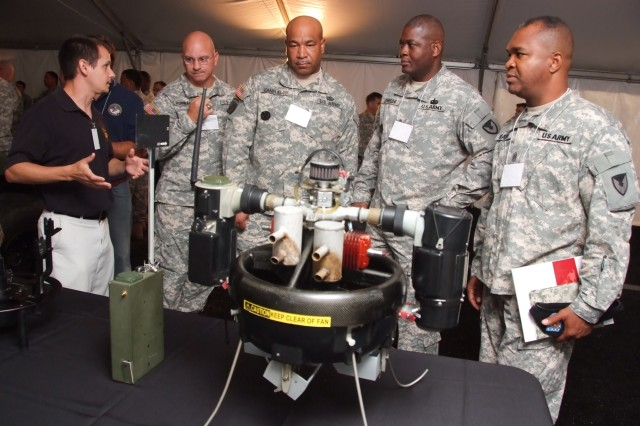 Michael Vitale, an engineer with CERDEC Night Vision Electronic Sensors Directorate, explains T-HAWK, an aerial sensor platform, and its role in the E09 Unified Battle Command study of the cognitive impacts of technology on Soldiers to Sgt. Maj. Steven Hornbach, RDECOM Army Research Labs; Command Sgt. Maj. Carl Campbell, 406th Army Field Support Brigade; Command Sgt. Maj. Tyrone Johnson, CECOM LCMC; and Command Sgt. Maj. Hector Marin, RDECOM.