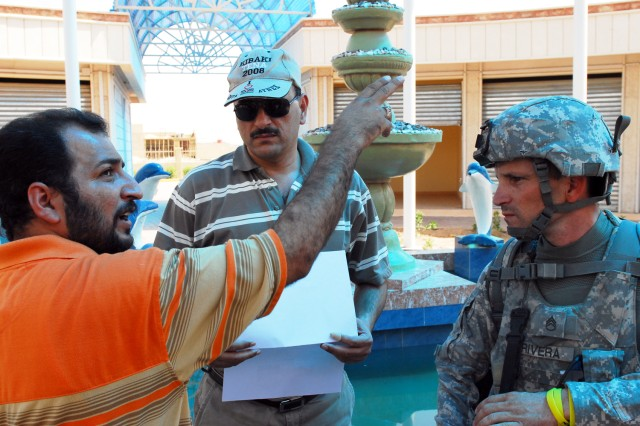 Abul Azariq Muhammad, (left), Iraq project manager for al Zaquri Group, discusses opening preparations for Basrah City's newest market with Staff Sgt. Hugo Rivera, 1314th Civil Affairs Company, Civil Liaison Team, 17th Fires Brigade. The market is slated to open later this month.