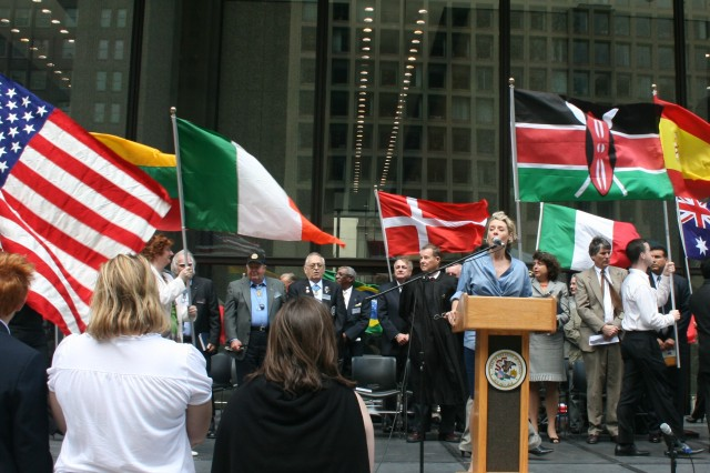Allison Ruble, USO of IL, sings the National Anthem to open up the city of Chicago's Naturalization Ceremony on Daley Plaza, while a parade of flags goes on behind her. Three Medal of Honor Recipients are recognized on stage before the ceremony, in front of about 300 attendees and all local media. The ceremony was hosted by the Mayor's Office of Special Events on Sept. 16, 2009.