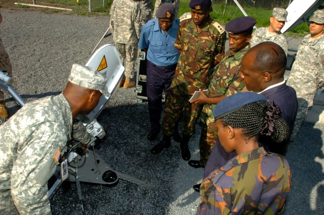 Sgt. 1st Class Anthony C. Tyler, a broadcast maintenance instructor with the Defense Information School, describes the functionality of a Digital Video and Imagery Distribution System satellite to public affairs personnel from the Kenyan Army during a visit to DINFOS in Maryland, Sept. 14. The Kenyan Army was invited as part of a public affairs exchange between Third Army / U.S. Army Central and Kenyan public affairs personnel. The purpose of the visit was to compare public affairs strategies between United States and Kenyan militaries and improve interoperability and cooperation between the partner nations.