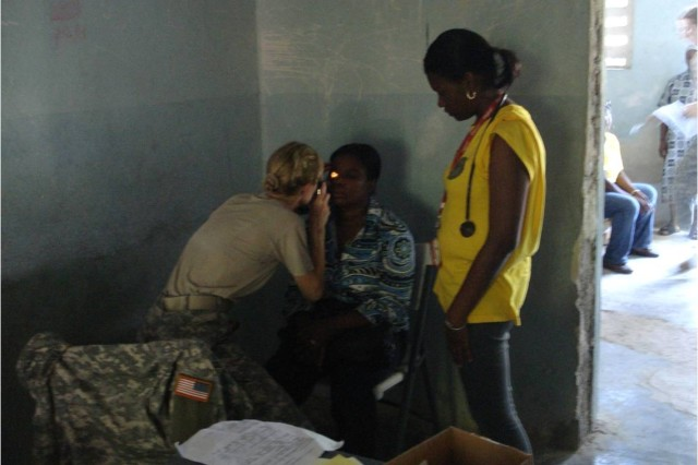 Lt. Col. Judith Driscoll, an optometrist with U.S. Army Reserve North East - Medical Area Readiness Support Group, conducts an eye exam with the assistance of a volunteer Haitian medical student at the Marigot's Ecolge Nationiale de Marigot in Haiti.  In addition to providing humanitarian assistance, medical training and readiness exercises also provides valuable experiences to learn from Haitians and civilian experts. This experience helps ensure the U.S. military is able to rapidly respond in support of emergency relief efforts in the future. (U.S. Army Photo by Sgt. First Class Manuel Zegarra, U.S. Army South/Released)