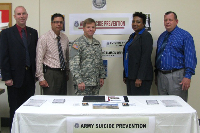 From left, Barrett Parris, Jose De Jesus, USASAC commander Brig. Gen. Christopher Tucker, Carol Morales and Gale Fenwick take a moment to look over the commandAca,!a,,cs suicide prevention information table.