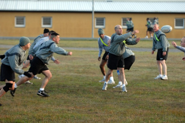 Col. Mark Calvert, 1st Armored Division, chief of staff, leads the charge toward Lt. Col. Randy Wardle, assistant chief of staff-communications, during a rugby match between officers at the Grafenwoehr Training Area Sept. 27. (Photo by Pfc. Jennifer Kennemer, 16th Mobile Public Affairs Detachment)