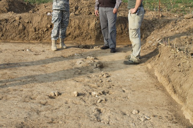 One of the students from the University of Mainz (right) explains the archeological dig efforts to Armed Forces Network personnel Sept. 22, 2009, during foundation work at a new townhouse project site at the southern end of the Wiesbaden Army Airfield in Germany. Remnants of a stone wall, among other items, were found on the construction site.