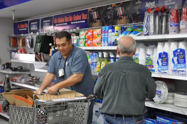 Leon Williams, Arsenal PX manager, stands to the left as fellow PX employee, Dave Carmel, dresses-right-dresses the shelves.  This small PX has already provided more than $19,000 to the Arsenal's MWR fund this year with one month to go.