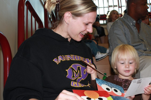 Mary Gruver and her 2-year-old daughter, Kaci, have fun with some of the free Sesame Street  goodies during the Sesame Street/USO Experience for Military Families performance in Mannheim Sept. 27. The Sesame Street tour also stopped in Kaiserslautern, Heidelberg and other locations throughout Europe. The free show was designed to educate military families about how to help children cope with the challenges of deployment.
