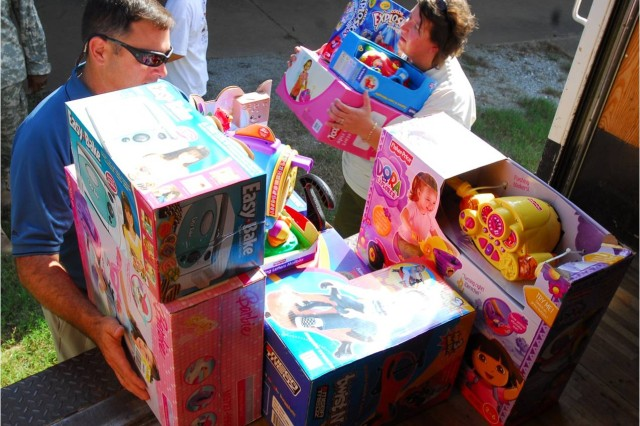Dan Packard, vice president of sales for Revision Eyewear, and Dottie Hiter deliver $5,000 worth of toys to Santa's Castle Tuesday.  The donation, which includes $16,001 in all, will be used to purchase toys for the charity, which helps families during the holiday season.