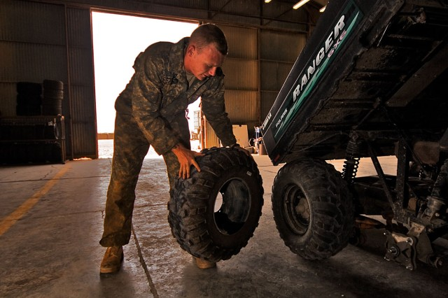 CAMP TAJI, Iraq-After replacing a half shaft, Spc. Brian Frye, from Fredericksburg, Va., a light wheel mechanic in Company E, 4th Battalion, 227th Aviation Regiment, 1st Air Cavalry Brigade, 1st Cavalry Division, begins a tire change on a Polaris, here, Sept. 28.