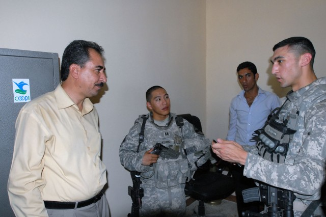 "TAJI, Iraq- Cambridge, Mass. native, Staff Sgt. Carlos Madden (right), a civil affairs team leader attached to the 1st Battalion, 82nd Field Artillery Regiment, and Little Rock, Ark. native, Capt. Alex Aquino (middle), commander of Battery B, speak to Dr. Mohammed (left), the manager of the Taji Market Clinic during a visit, Sept. 27. The ""Dragons"" visited the clinic to see if they could help provide any supplies and support to the clinic."