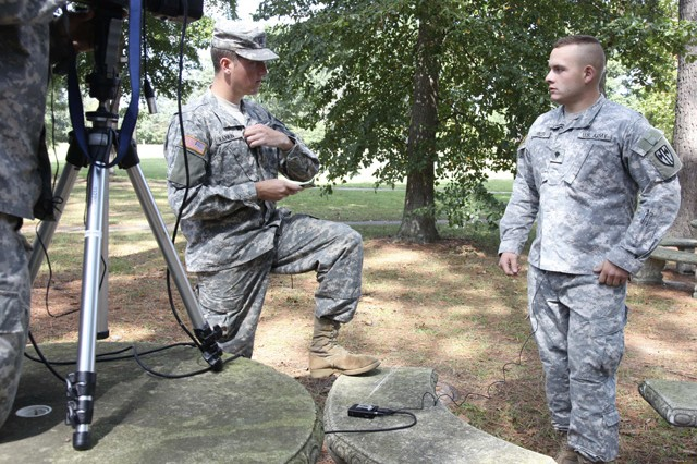 Spc. Bryan Rankin, 55th Combat Camera, helps Spc. Daniel Micek, U.S. Army Europe, prepare for media interviews during the Best Warrior Competition on Fort Lee, Va. Sept. 29, 2009. During the competition, these elite competitors test their Army aptitude by conquering urban warfare simulations, board interviews, physical fitness tests, written exams, and Warrior tasks and battle drills relevant to today's operating environment.
