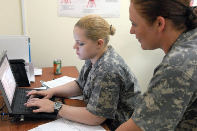 CAMP TAJI, Iraq - Pfc. Dominka Jakubczak (left), of Yuma, N.M., enters data into a computer system, Sept. 24, after screening patients at the Hale Koa Medical Facility, here, with help from Spc. Anna Hatfield (right), from Conroe, Texas.  Both medics are with Company C, 115th Brigade Support Battalion, 1st Brigade Combat Team, 1st Cavalry Division.
