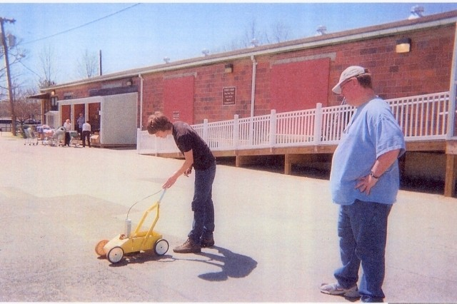 Nick Kellogg tests a pavement marker at the Fort Belvoir Thrift Shop parking lot as Scoutmaster Mark Funk watches. Kellogg's project cleaned the lot and restored lines that had been faded and made the lot unsafe and difficult to use.
