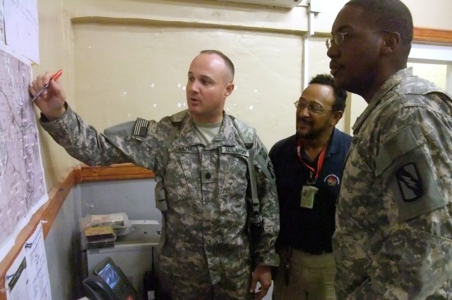 During a July 24 planning meeting, Lt. Col. William B. Smith, Jr. (left), COL Q-West Mayor, outlines a mission to catalog valve boxes and major taps on the Q-West water pipeline to Reinaldo Guebara (middle), a civilian contractor and Capt. James Hatcher Jr., officer in charge of the Mayor Cell Water Team.