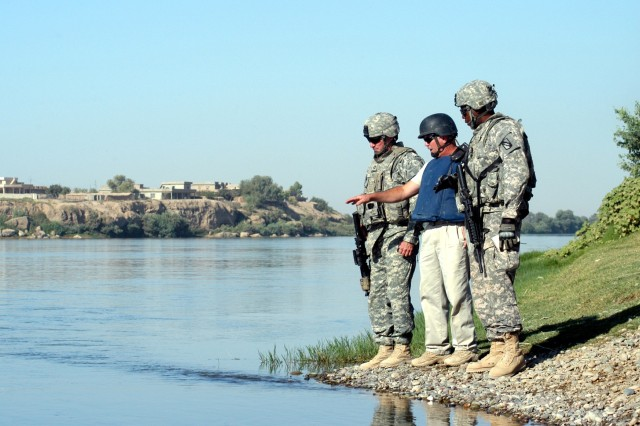 Capt. Drew Clark (left), force protection company commander of Madison, Miss., Buddy B. Winborn (middle), facilities supervisor and native of Alma, Ark., and Capt. James Clark, Water Team officer-in-charge from Clarksville, Tenn., debate the feasibility of pumping water from the Tigris River at a location closer to Q-West during a reconnaissance mission Aug. 11.