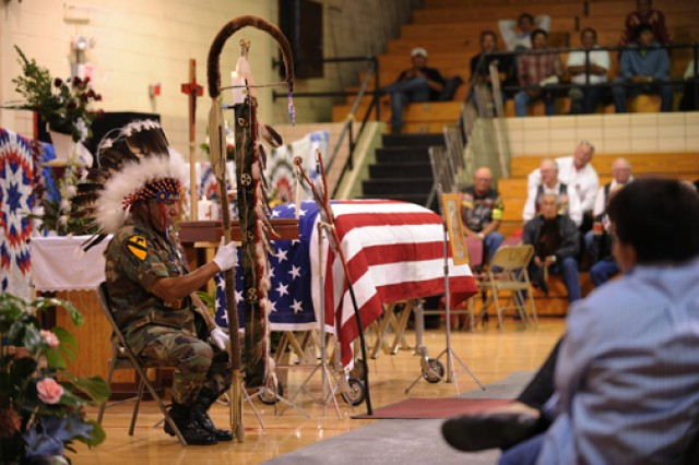 """Larry Hale, a member of the Red Feather Society, guards the flag-draped casket of Sgt. 1st Class Arthur F. """"Bluie"""" Jewett at his funeral held in Eagle Butte, S.D., on Sept. 25. Jewett, a member of the Cheyenne River Sioux Tribe, was killed in action during the Korean War's Chosin Reservoir campaign."""