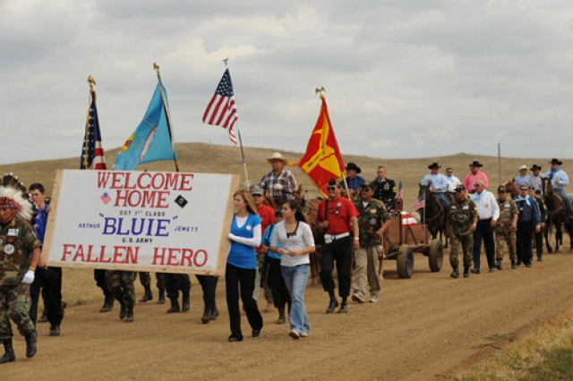 """A flag-draped casket holding the remains of Sgt. 1st Class Arthur F. """"Bluie"""" Jewett rides in the back of a horse-drawn wagon, escorted by family members and friends, to St. Theresa Catholic cemetery near White Horse, S.D., Sept. 25. Jewett, a member of the Cheyenne River Sioux Tribe, was killed-in-action during the Korean War's Chosin Reservoir campaign and his remains were not identified until earlier this year."""