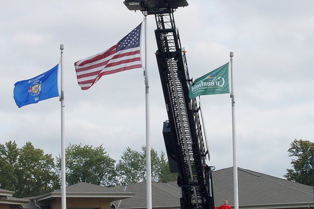 MILWAUKEE -- Staff Sgt. David Castaneda, a recruiter with the U.S. Army Milwaukee Recruiting Battalion, re-enlists while suspended more than 40 feet above ground on the bucket of a fire truck ladder Thursday, Oct. 1, at the Greenfield Fire Department. Castaneda, a Milwaukee native, is an Army firefigther. His father has been a Milwaukee firefighter for 23 years and his uncle retired from the Milwaukee Fire Department. Maj. Michael Sheehan, the battalion\'s executive officer, administers the oath of enlistment. Photo by Jorge Gomez.