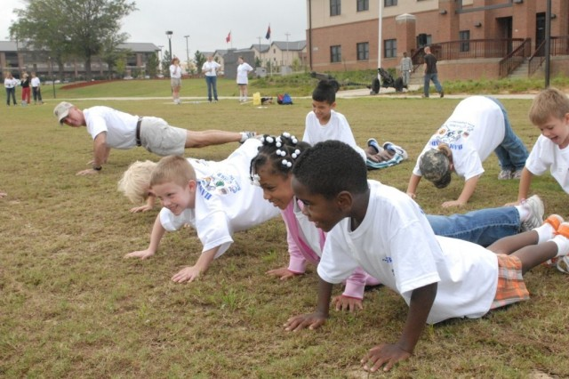 Col. Peter Jones, commander, 3rd Heavy Brigade Combat Team, 3rd Infantry Division, practices push-ups with children of 3rd HBCT Soldiers during a Kid's Deployment Camp on Kelley Hill, Fort Benning, Ga., Sept. 19.