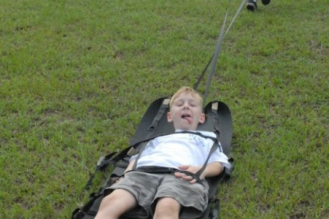 David Priatko, 8, drags Jason Penosky, also 8, on a litter during a Kid's Deployment Camp on Kelley Hill, Fort Benning, Ga., Sept. 19. The litter was one of many pieces of military equipment the kids learned about during the two-day camp designed for children of the 3rd Heavy Brigade Combat Team.