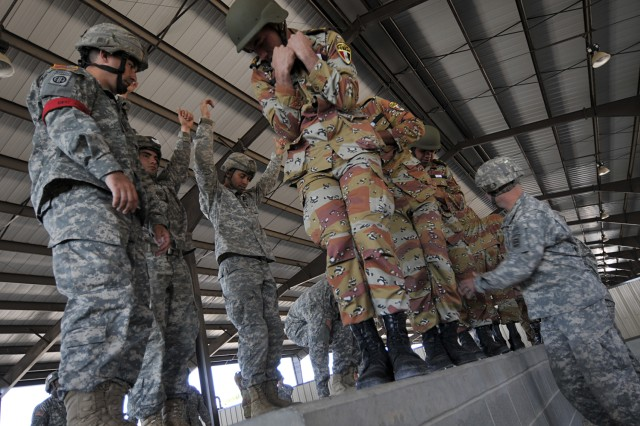 "Sgt. 1st Class Chad Louis (left), of 1st Battalion, 325th Airborne Infantry Regiment, 2nd Brigade Combat Team, 82nd Airborne Division, supervises as American and Egyptian paratroopers practice parachute landing falls at Pope Air Force Base prior to a ""friendship jump"" airborne operation featuring airborne forces from five countries. The jump was part of the Bright Star Exercise, a joint, multi-national training exercise being held at Fort Bragg, N.C. from Sep. 28-Oct. 12."