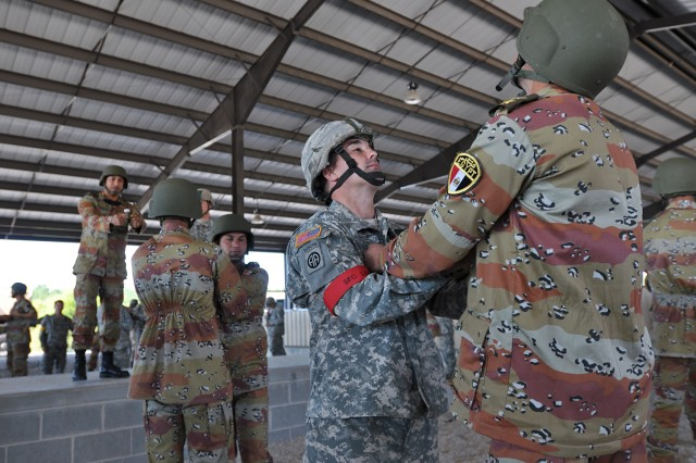 "Sgt. 1st Class Chad Louis, of the 1st Battalion, 325th Airborne Infantry Regiment, 2nd Brigade Combat Team, 82nd Airborne Division, practices escaping from a parachute entanglement with a paratrooper from the Egyptian Army prior to a ""friendship jump"" airborne operation featuring airborne forces from five countries. The jump was part of the Bright Star Exercise, a joint, multi-national training exercise being held at Fort Bragg, N.C. from Sep. 28-Oct. 12."