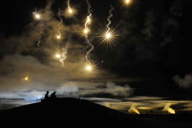 Participants in the Department of the Army Best Warrior Competition fire at targets as the night sky is illuminated with simulated munitions, adding a breath of realism to the night-fire event.  The competition was held at Fort Lee, Va.