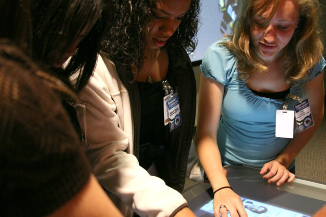 Dakota Wood (center) works to solve a puzzle with her West Limestone High School classmates. The rest of the students were able to view their attempts on the screen behind Wood.